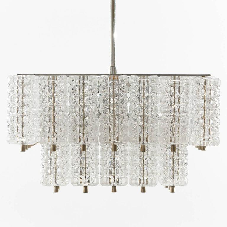 A square Austrian glass and chrome chandelier by Austrolux, 1960s.  Large glass blocks are mounted on a silver painted metal frame. The light is similar to the products of Kalmar. The fixture has sockets for six small screw base bulbs.  It is