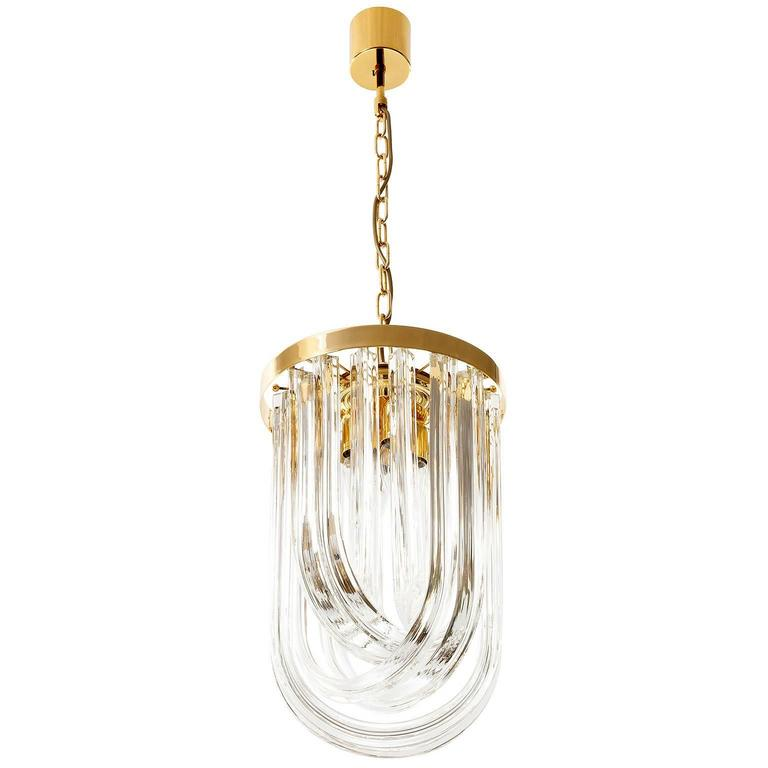A wonderful Italian hollywood regency pendant light by Venini manufactured in Mid-Century in the 1960s. It is made of pairwise curved crystal Murano glasses in different lengths and a gold-plated brass frame. Excellent condition.  The height of the