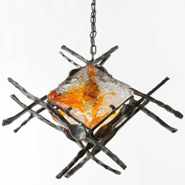 A Brutalist style handmade iron and glass light fixture, manufactured in Mid-Century, circa 1970.  This modernist lamp is made of wrought iron and two handblown orange / amber tone glasses. It can be used as pendant or wall light. The light has one