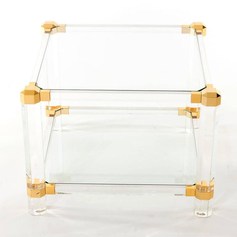 A cocktail or side table in the style of Pierre Vandel, Paris, France, manufactured in Mid-Century in 1970s. It is made of Lucite, glass and gilded parts.