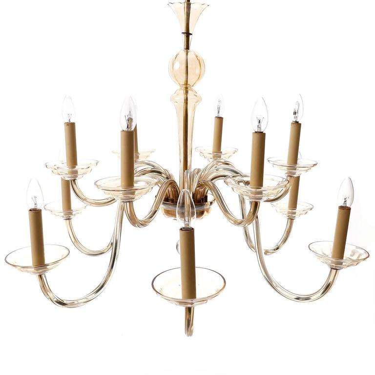 A beautiful and large Art Deco light fixture by J.L. Lobmeyr, Vienna, Austria, 1930s. This chandelier has twelve arms with sockets for candelabra E14 screws base bulbs (LED or filament). It is made of brass with lovely natural aged patina and