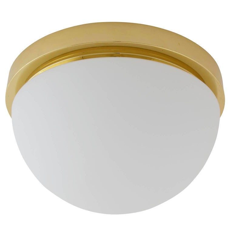 One of four flush mount lights or sconces by Glashütte Limburg, manufactured in midcentury, circa 1970. They are made of a polished brass armature with a dome shaped opal glass lampshade. Labelled with Glashütte Limburg. The price is per light. They
