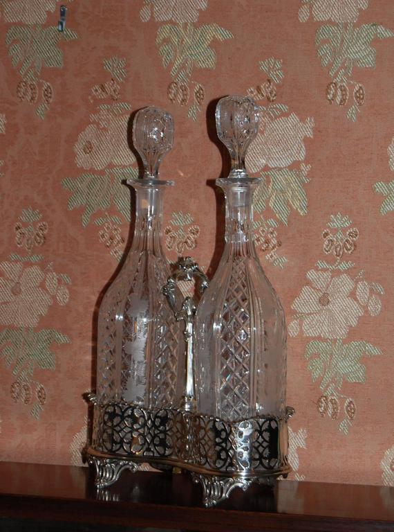 Silver plated Tantalus with two cut-glass decanters with original stoppers, in a Classic English style, circa 1850. The decanters are quality cut-crystal with beautifully engraved decorations of grape leaves and vines.