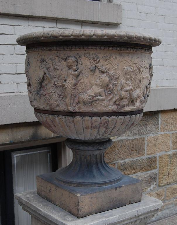 This large terracotta urn shows playful children and goats frolicking, as well as continual grape vines and trees around the entire perimeter. It has two steel retaining rings mounted to secure the urn and to keep the existing stress crack from