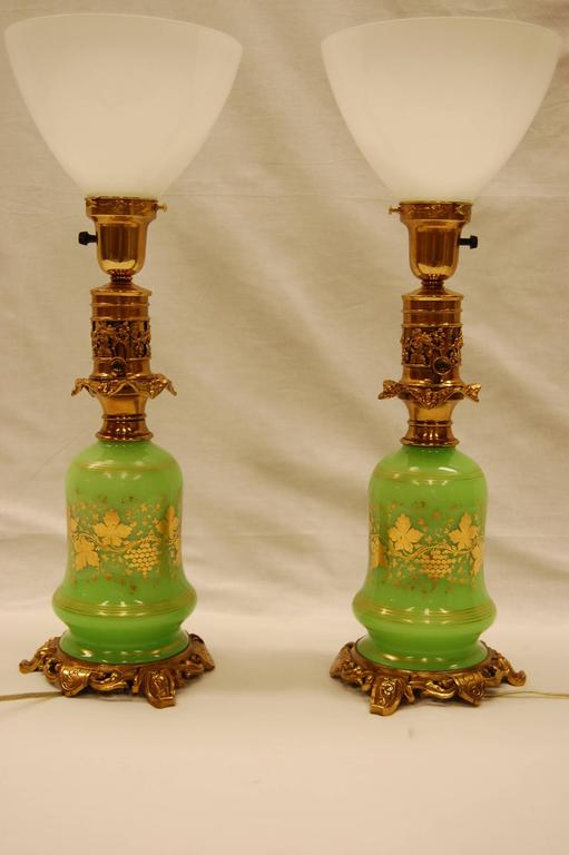 Pair of opaline oil lamps with gold leaf grape leaf decorations, recently rewired with three-way sockets. Completely cleaned and lacquered brasses. Measure: 14 inches to the top of the oil font. With original brass fittings.