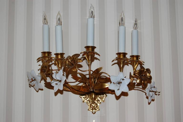 Pair of French wall sconces with brass flowers and leaves and white opaline glass lilies, recently wired with white metal candle covers.