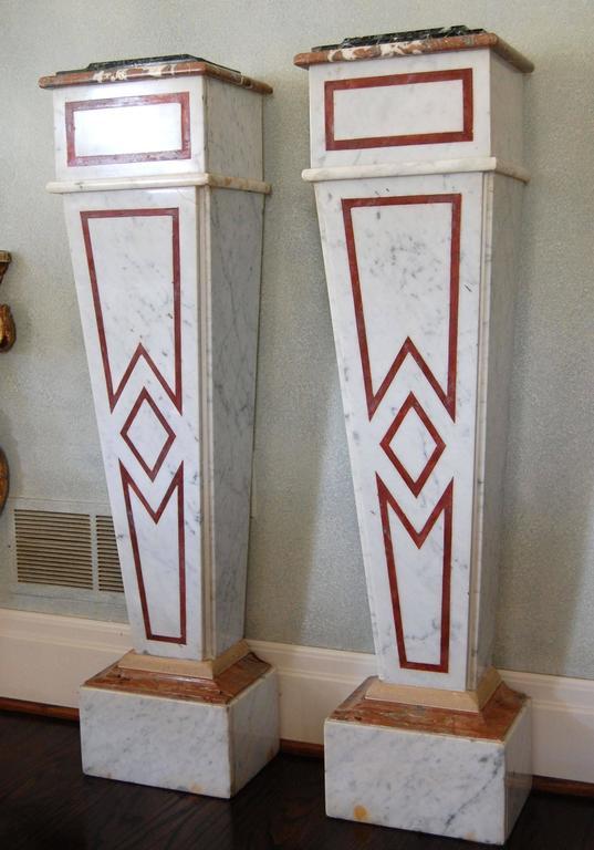 Elegant pair of marble pedestals comprised of; column: white Carrara with French rouge antique feature strip; white Carrara base with Duquesa Rosa sub cap and Beauharnais cap; Duquesa Rosa cap with Verde antique top.