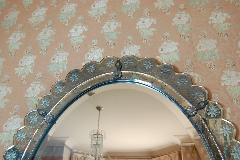 Exquisite oval mirror 4' tall and 3' wide, with a 1 1/8 inch wide bevel on the center piece of glass. The border is all wheel-cut in a floral design, on blue gray glass. There is minimal marking on the reverse side of the mirror, as shown in the