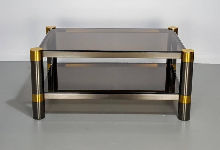 Karl Springer coffee table in rare gunmetal and gold tone finish, signed, 1970s. Glass has a smoked amber tint. Condition is excellent with less than average wear for age and use.  See this item in our private NYC showroom! Refine Limited is located