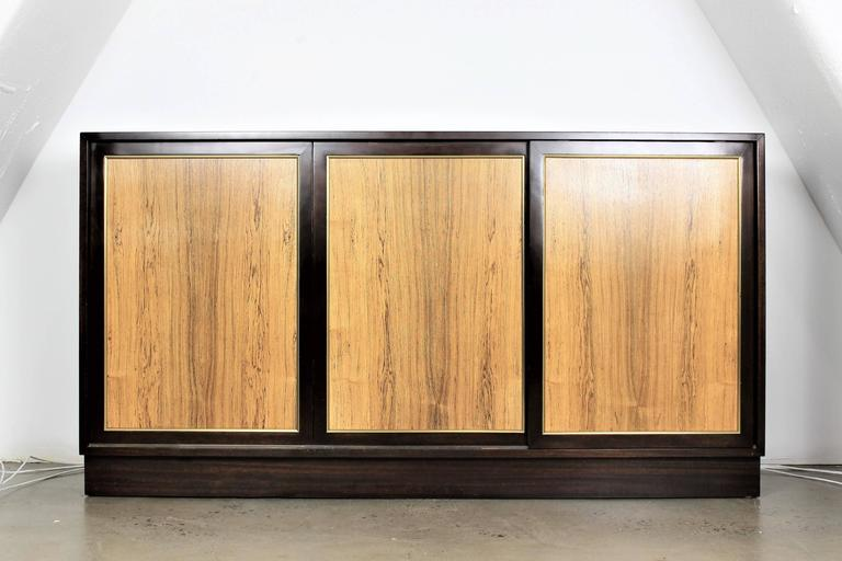 Dresser or Buffet by Harvey Probber in dark mahogany with rosewood sliding doors, 1960s. Classic design and lots of storage.   Whether furnishing a contemporary Soho loft or stylish post-war Park Avenue penthouse, an artistic Central Park townhome
