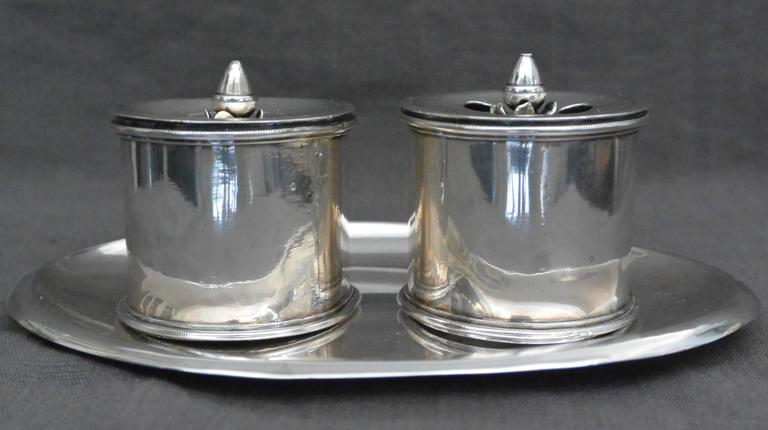 Roman sterling silver inkstand of sober neoclassical form comprising double pots for sander and inkwell with acorn finial lids on a stamped oval tray, Italy, early 1800s.