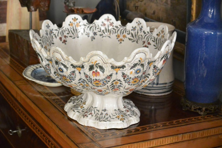Very large Bassano centerpiece bowl of footed monteith form. Decorative floral sprays and swags throughout the twelve lobes and footed base as well as large bouquet on interior. Underglaze blue marks for Bassano. Italy, circa 1840. Dimensions: 18