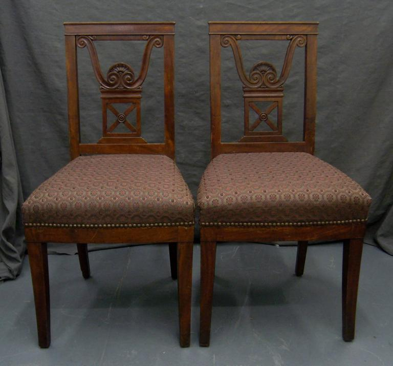 Pair of Jansen hall chairs with neoclassical anthemion carved open back, newly upholstered in aubergine horsehair, France, circa 1940.