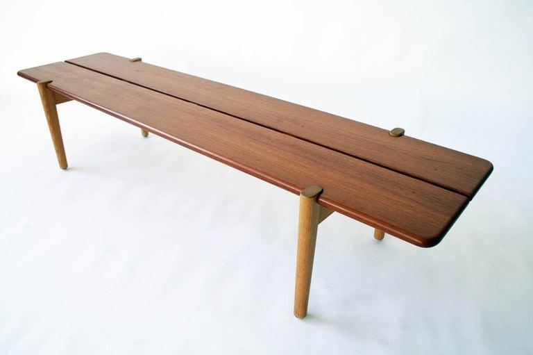 Hans Wegner teak and ash bench for Johannes Hansen, Denmark, 1950. Excellent condition. Dimensions; 67 W x 18 D x 14 H in (170 × 46 × 36 cm)  Literature: Hans J. Wegner's 100 Chairs, Oda, pg. 44 Wegner: En Dansk Møbelkunstner, Møller Nielsen, pg.