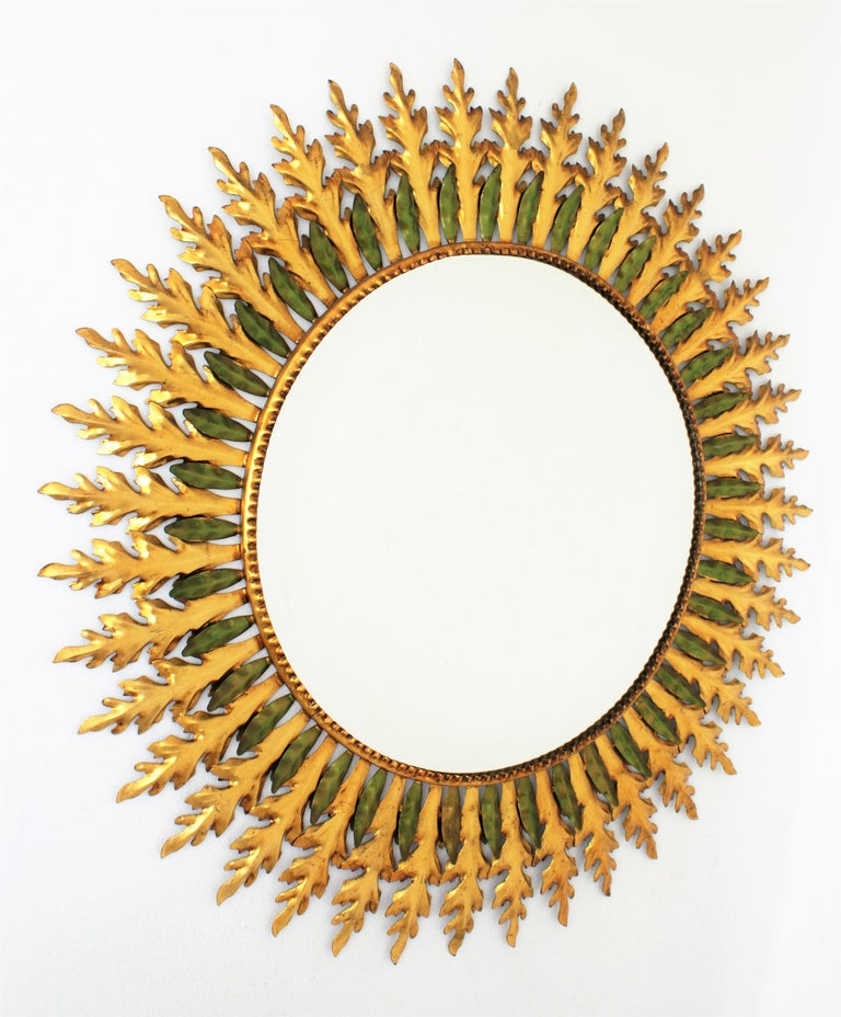 Outstanding 100 cm diameter Hollywood Regency gilt iron double layered sunburst mirror. This magnificent sunburst wall mirror has a layer of gilt iron large leaves and a layer of small green patinated leaves. Measures: Glass diameter 57cm.