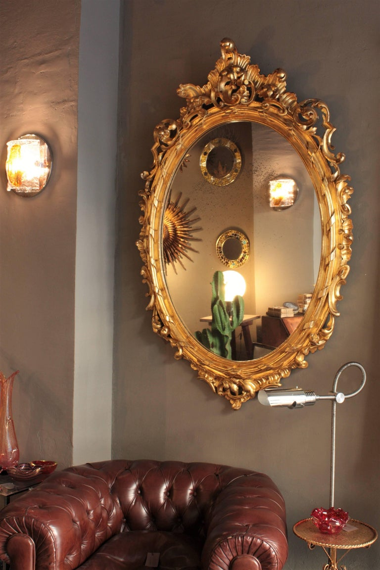 An spectacular and finely carved palatial Rococo style mirror with gold leaf finish in a very big size. A superb example of gilt Rococo style framework.