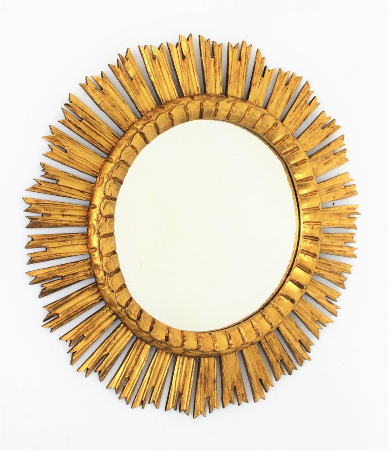 Gorgeous finely carved gold leaf giltwood sunburst mirror. This mirror is in excellent condition, it has a very beautiful patina and wears its original glass. France, 1930s. Interesting to be placed alone or creating a wall composition with other