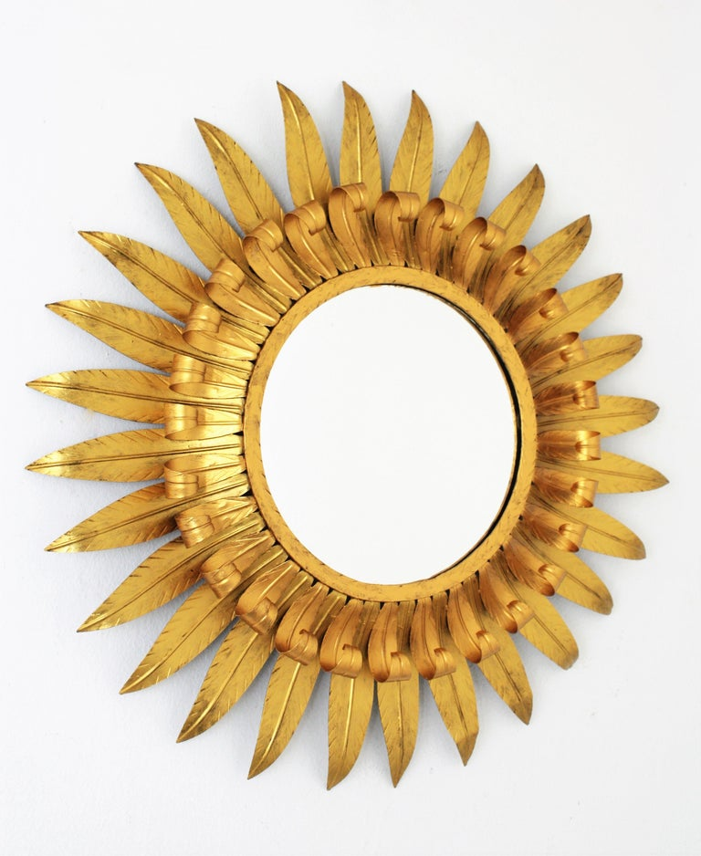Spanish gilt iron eyelash sunburst mirror with gilt patina in two golden tones. This mirror has two layers of beams, one of them with eyelash shape. The bicolor tones highlight it beauty. Spain, 1960s. Glass diameter: 28cm