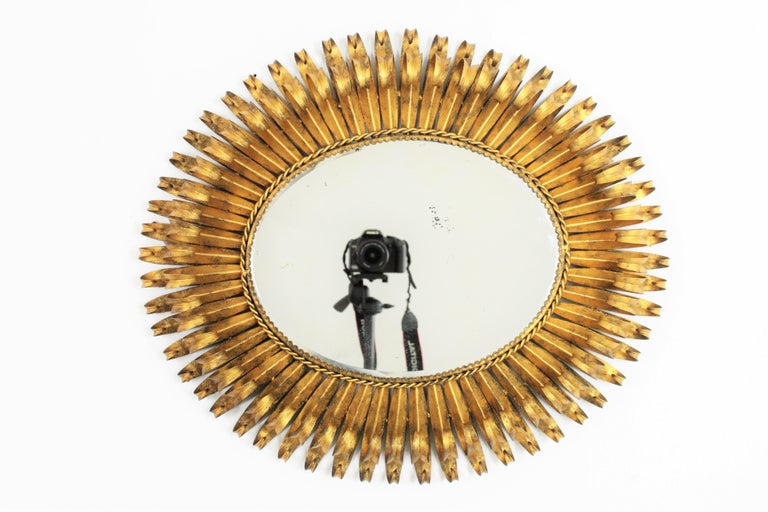 Beautiful hand-hammered Brutalist gilt iron oval shaped sunburst mirror with a highly articulated double layered eyelash frame. It can be placed in two positions, Spain, 1950s.