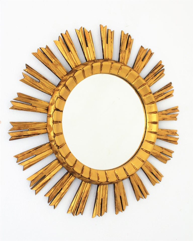 A lovely sunburst or starburst mirror with a beautiful original patina. The mirror is made in carved wood, covered with gesso and has gilt finish. France, 1930s. Glass diameter: 26cm. Lovely to be placed creating a wall composition.