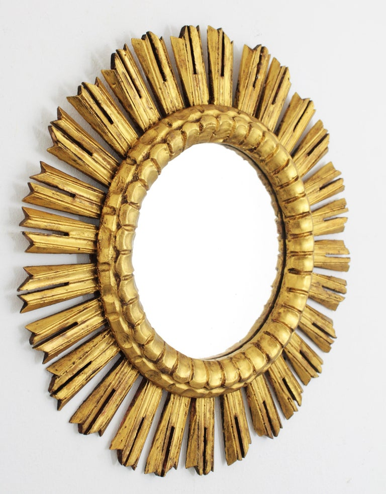 Amazing French giltwood sunburst mirror with gold leaf finish. Finely carved piece and charming patina. Original glass mirror, France, 1930s. Dimensions of the glass: 24 cm diameter. Lovely to be placed creating a wall composition with other