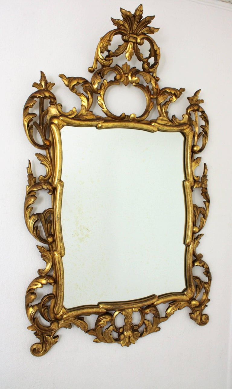 A finely carved and highly decorative Rococo style mirror with gold leaf finish and beautiful original patina. Frame with details of scrolled acanthus leaves and an important carved crest. This mirror is in excellent condition and it has been