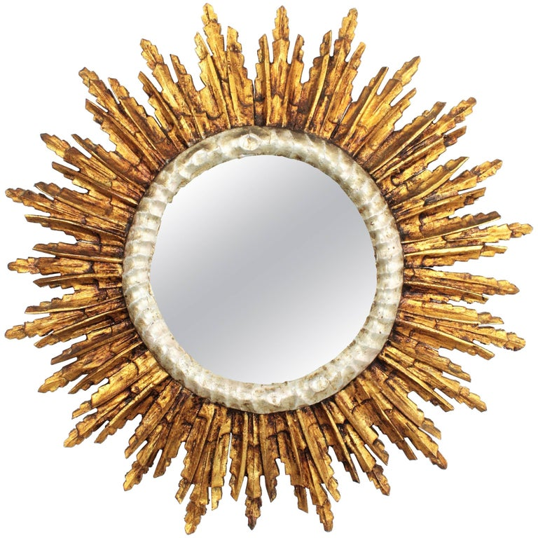 Magnificent hand carved wood mirror in Baroque style with silver leaf finish surrounding the glass and gold leaf finish at the frame. The mirror has a gorgeous patina and it is in excellent condition, France, 1930-1940. Dimensions of the glass