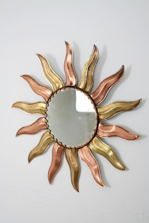 Midcentury copper and brass French sunburst mirror.  France, circa 1950.  Lovely to place alone but also beautiful placed in a wall decoration with other sunburst mirrors.