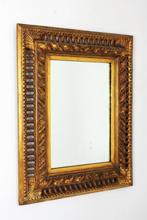 A finely carved Spanish Baroque style giltwood mirror with reticulated frame. The frame has a very beautiful hand carved work with an amazing patina. Gold leaf finish over Ghesso, Spain, circa 1880.  Useful also to frame a picture.