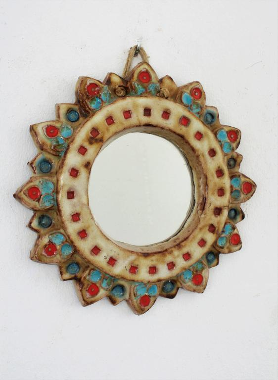 A colorful glazed ceramic sunburst mirror in ivory color with colorful blue, green and red accents from La Roue-Vallauris in the manner of Georges Pelletier.  Signed La Roue on the back. France, 1950s.