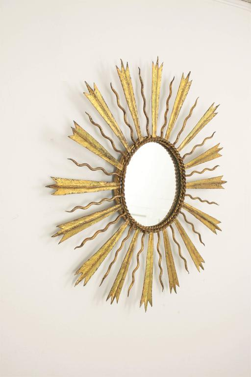 Lovely hand-hammered gilt iron sunburst mirror with combined beams in the style of Gilbert Poillerat, France, 1930s.  Beautiful to place it alone or to create a wall decoration with other mirrors in this manner. Avaliable a huge collection of