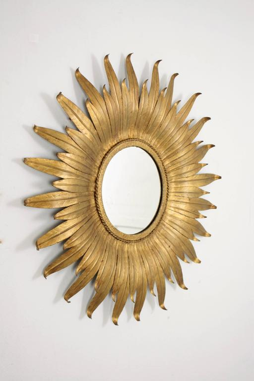 A lovely sunburst or flower burst mirror handcrafted in Spain at the mid-20th century period. A circular glass framed with curved gilt leaves in two sizes. This pieces wears its original vintage patina. Spain, 19650s-1960s. A beautiful piece to