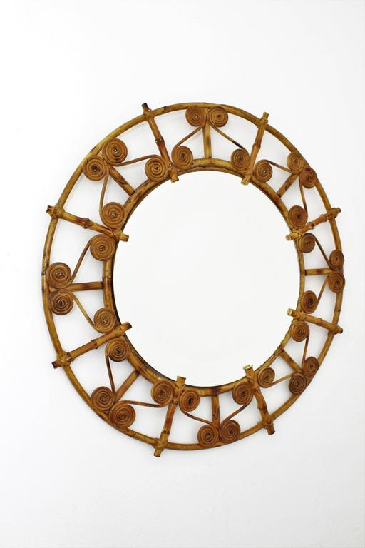 Lovely handcrafted bamboo and rattan mirror with a decorative frame with filigree details. Beautiful to place alone or in a wall decoration with other mirrors in this manner, Spain, 1950s.   Avaliable a huge collection of cane mirrors and other