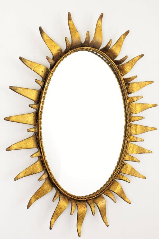 A huge and heavy wrought iron sunburst mirror with decorated beams in two sizes and gold leaf finish. This piece wears its original vintage patina and has all the taste of the Hollywood Regency style. Spain, 1950s. Beautiful to place it alone o to
