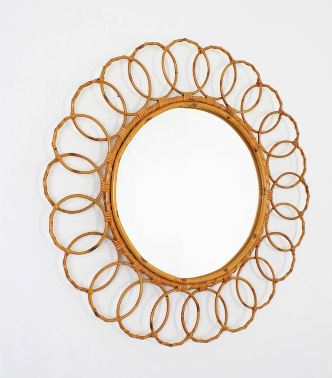 A handcrafted bamboo and rattan mirror framed with circles. This piece has all the taste and freshness of the Mediterranean style. Excellent vintage condition, Spain, 1960s.  Beautiful to place alone or with other cane mirrors to create a fresh