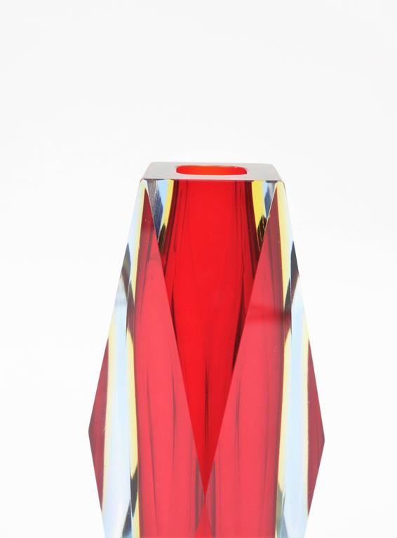Beautiful faceted Sommerso triple cased rubi red, yellow and blue Murano glass vase attributed to Mandruzzato. The vibrant colors make this piece highly decorative.