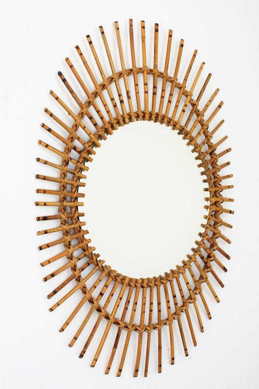 Vintage rattan or wicker oval shaped asymmetric sunburst mirror. This piece has all the taste of the Mediterranean coast style and it is in excellent vintage condition. France, 1960s. Beautiful to place in a wall decoration with other cane mirrors