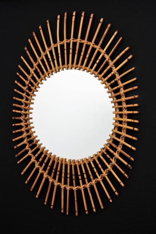 Hand-Crafted 1960s French Rattan Asymmetric Oval Sunburst Mirror For Sale