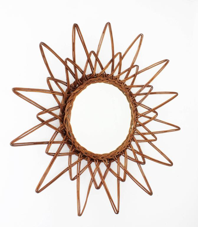 A beautiful handcrafted rattan or wicker starburst mirror. A highly decorative piece with short and long beams, star shape and beautiful color.