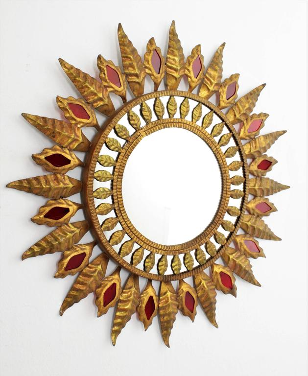 An unusual Hollywood Regency style gilt iron sunburst mirror with a mirrored surface surrounding the central glass and a lovely frame with gilt iron leaves alternating with small red glass accents,