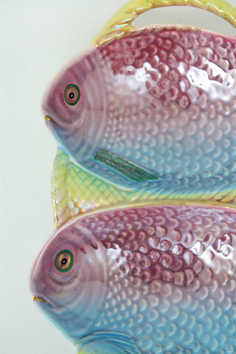 A colorful Portuguese pink, blue, yellow and green pastel colors glazed ceramic platter with two fishes and a highly decorative iridiscent effect. Mark from the manufacturer at the back. Portugal, 1960-1970.   Available more ceramic and