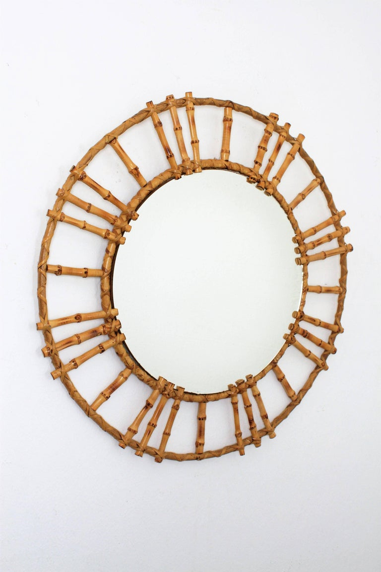 A sunburst mirror handcrafted in bamboo cane with a double circular cane frame surrounding the glass. A beautiful piece with oriental accents but all the taste of the fresh Mediterranean style. It wears the label from the manufacturer at the back