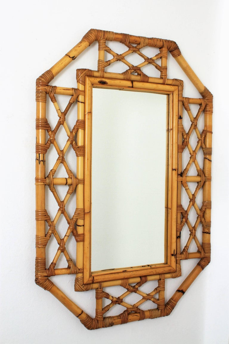 A handcrafted bamboo cane mirror with an interesting filigree work at the frame and Tiki or oriental accents. 