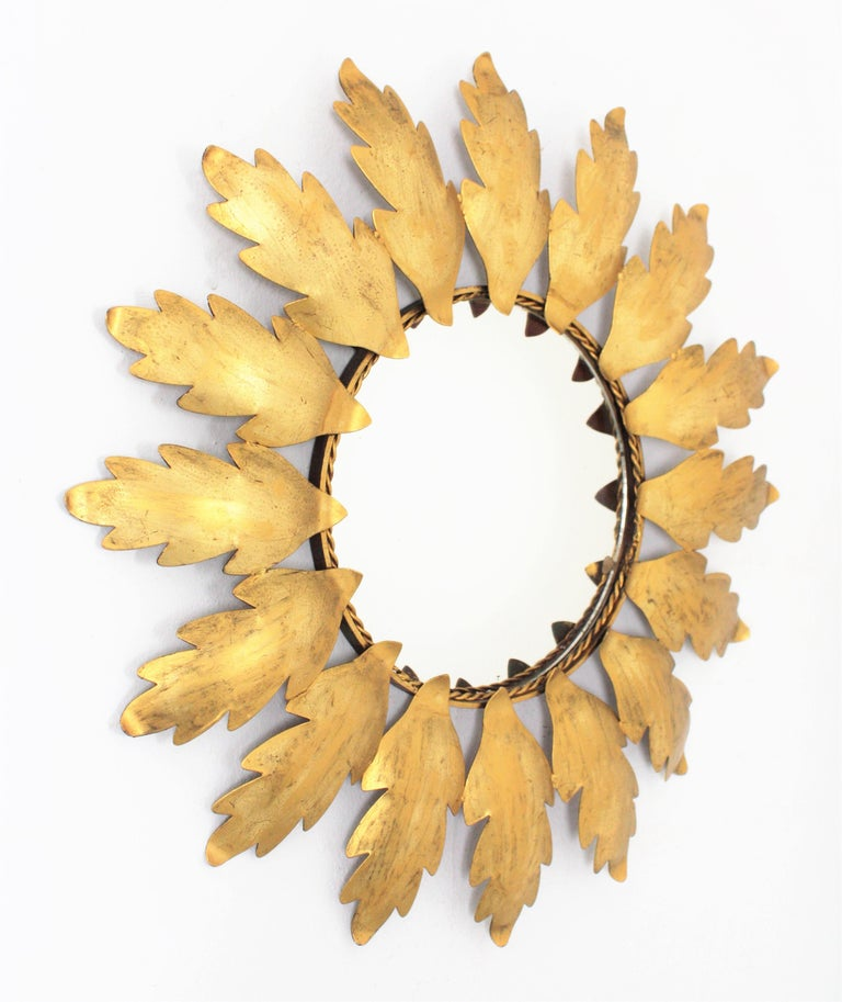Beautiful handcrafted gilt iron sunburst mirror. It has Leaves surrounding a central round glass in sunburst or flower shape disposition. Spain, 1960s. Diameter of the glass: 22 cm.