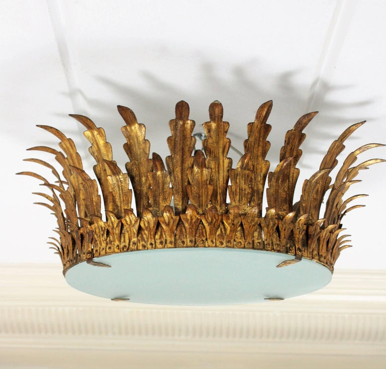 Large neoclassical style three-light hand-hammered gilt iron ceiling light fixture with gold leaf finish. This magnificent piece has three layers of leaves placed in the shape of a crown or sunburst and a frosted glass diffuser that can be easily