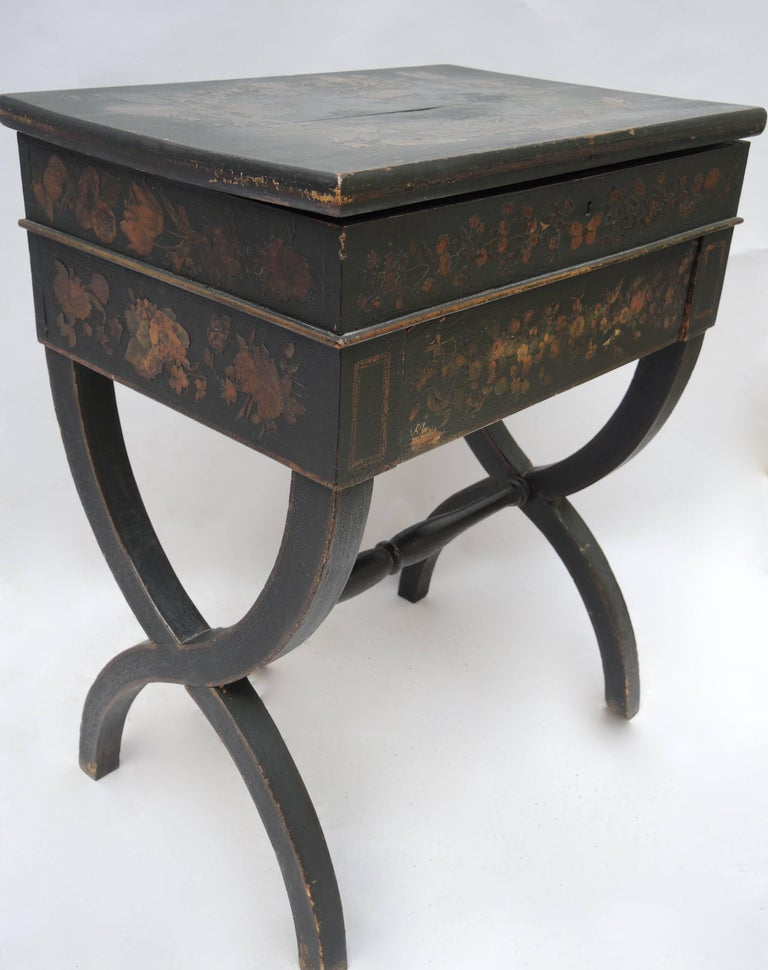 Black English Regency side table or dressing table with applied decoupage decoration of flowers, and insects. The top lifts up to revala robins egg blue painted interior with two compartments and a mirror. A lovely and versatile table in the