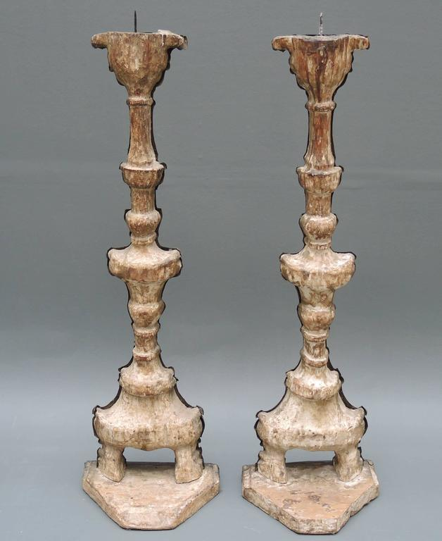 A pair of 18th century Italian altar candlesticks with repoussé brass work over wood. They can be made into table lamps by request at no extra charge. Repoussé is a metalworking technique in which a malleable metal is ornamented or shaped by