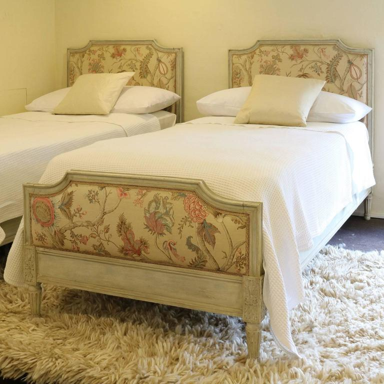 A Matching Pair Of Twin Upholstered French Beds In The Louis XVI Style With Distressed Painted