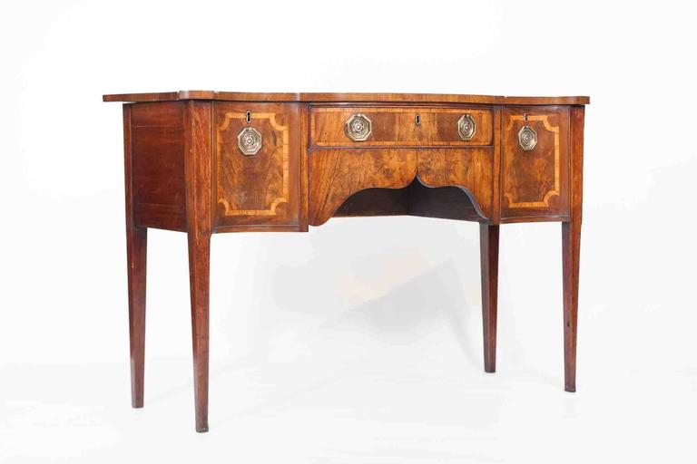 18th century walnut serpentine sideboard in the style of Sheraton, the pair of cellared drawers with inlaid and crossbanded decoration, centred by a short drawer above carved shaped apron terminating on square tapered legs.