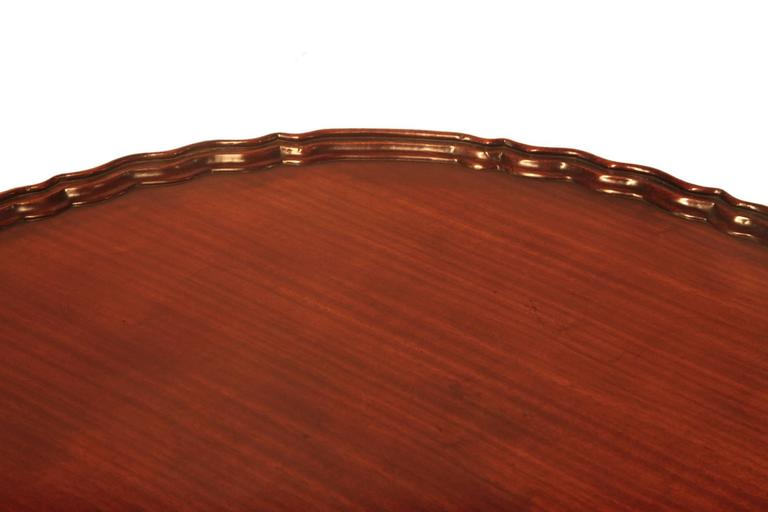 19th century George III tip up tea table, it has a scalloped mahogany top above birdcage pod with acanthus leaf carving on three shell carved legs.